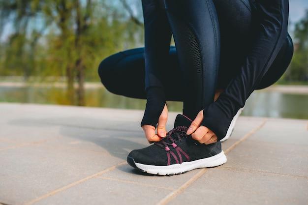Vista de cerca de las manos de la mujer en traje deportivo atarse los cordones de sus zapatillas deportivas mientras se ejecuta en el parque
