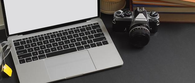 Vista de cerca de la mesa de trabajo con ordenador portátil, cámara en la oficina en casa