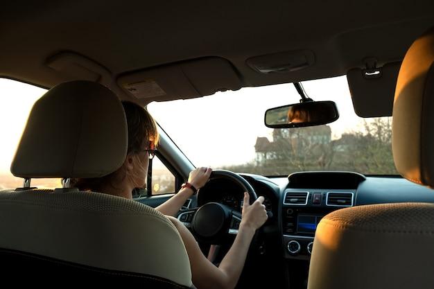 Vista de cerca de una mujer conductora sosteniendo el volante conduciendo un coche al atardecer.