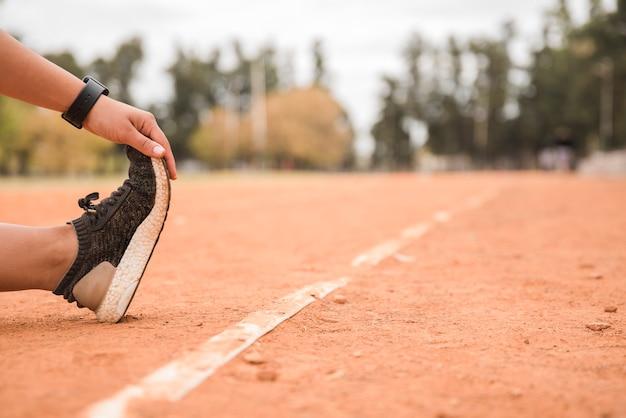 Vista de cerca de mujer deportiva estirando en pista de estadio