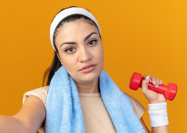 Vista de cerca de la mujer deportiva joven confiada con diadema y muñequeras levantando mancuernas estirando la mano hacia el frente mirando al frente con una toalla alrededor del cuello
