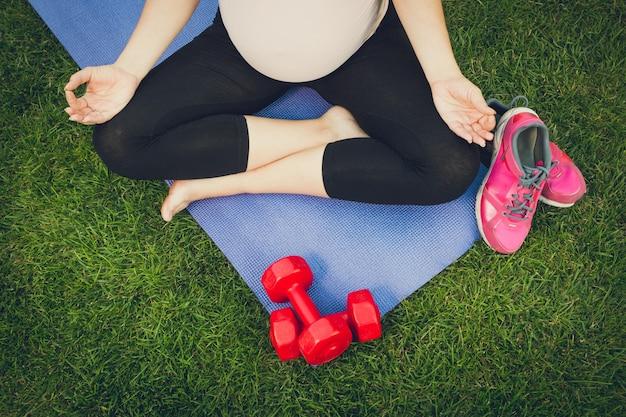 Vista de cerca de la mujer embarazada meditando sobre estera de fitness en el parque