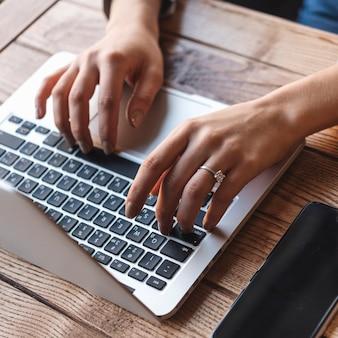 Vista de cerca de mujer escribiendo en portátil en cafetería