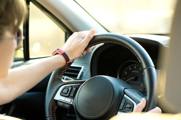 Vista de cerca de la mujer que sostiene el volante conduciendo un coche en las calles de la ciudad en un día soleado