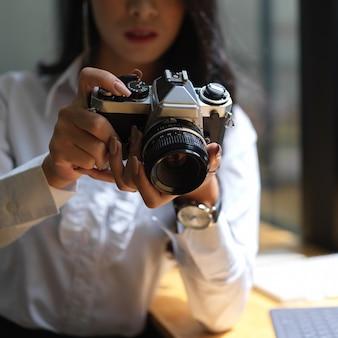 Vista de cerca de mujer tomando fotos con cámara digital mientras trabaja en estudio