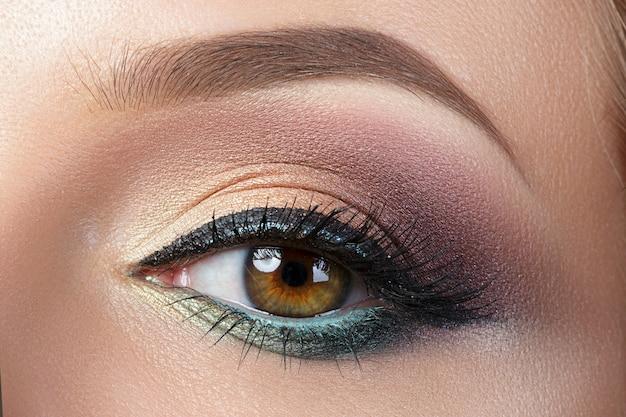 Vista de cerca del ojo femenino marrón con maquillaje de noche. ojos ahumados coloridos con delineador de ojos negro.
