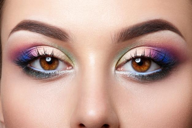 Vista de cerca de ojos marrones femeninos con maquillaje de ojos ahumados de color rosa y azul colorido