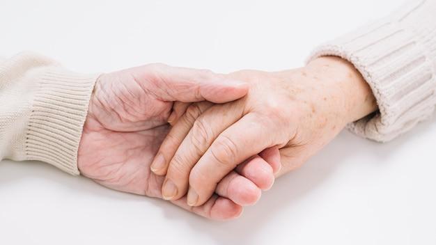 Vista de cerca de pareja mayor cogiéndose las manos