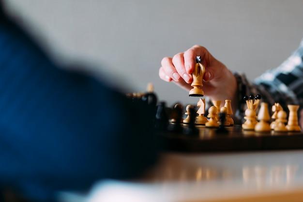 Vista de cerca pareja mayor jugando ajedrez en casa de ancianos