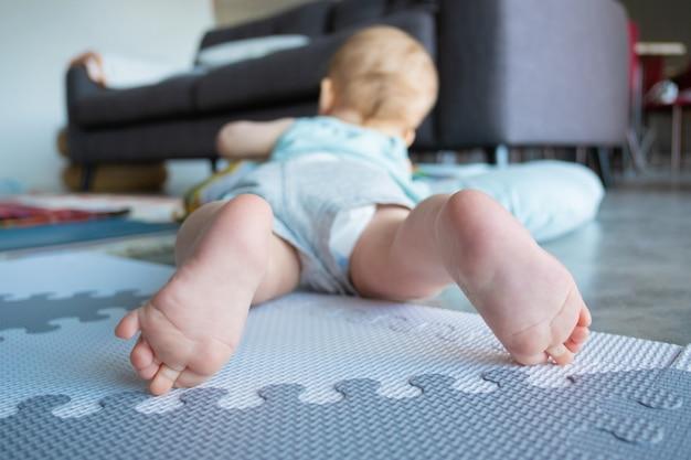Vista de cerca de las piernas o los pies de un bebé pequeño. lindo bebé adorable acostado boca abajo y jugando en un piso blando en casa. concepto de infancia e infancia.