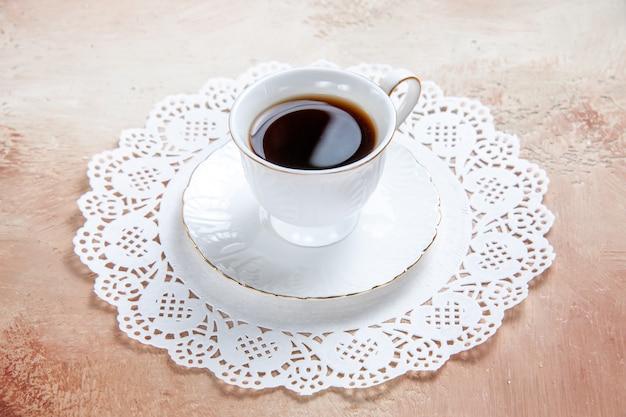 Vista de cerca de una taza de té negro sobre una servilleta decorada en blanco en colores