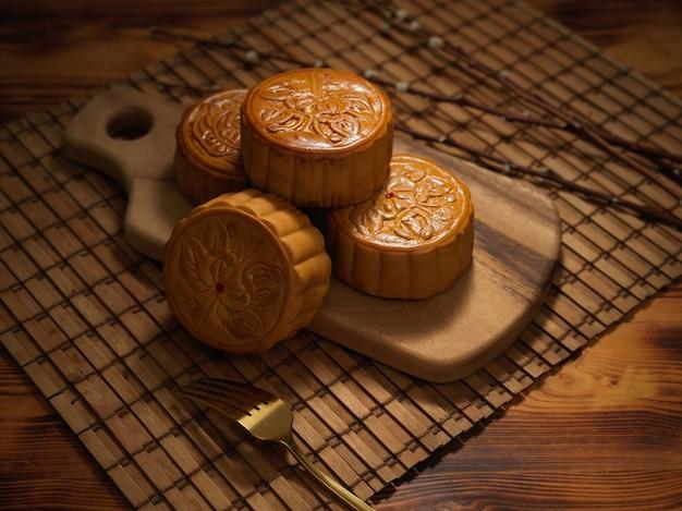 Vista de cerca de los tradicionales pasteles de luna sobre tabla de madera y tenedor en mantel de bambú. el carácter chino en el pastel de luna representa