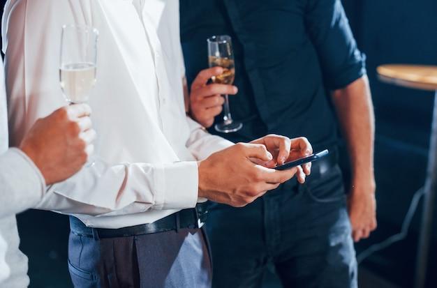 Vista de cerca de tres chicos con ropa de fiesta que conversan y miran el teléfono.
