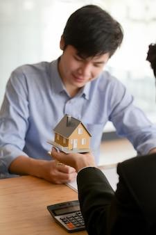 Vista cercana del agente de bienes raíces sosteniendo el modelo de la casa mientras se presenta al cliente masculino