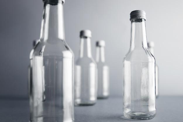 Vista cercana de botellas de vidrio vacías transparentes sin etiqueta para bebidas frías y bebidas