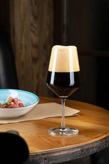 Vista cercana de cerveza artesanal oscura y fría en un vaso con merienda en el bar en la mesa