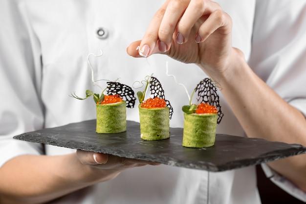 Vista cercana del chef sosteniendo un plato de comida