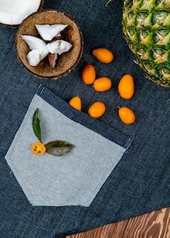 Vista cercana de cítricos como coco medio cortado con rodajas de coco en cáscara kumquats piña con hojas sobre tela de jeans y fondo de madera