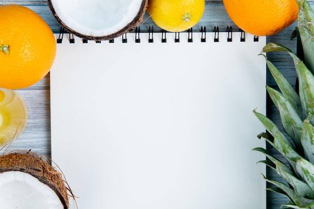 Vista cercana de cítricos como naranja, coco, mandarina, piña, limón con bloc de notas sobre fondo de madera con espacio de copia