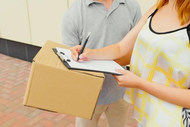 Vista cercana del cliente que firma un recibo del paquete de entrega