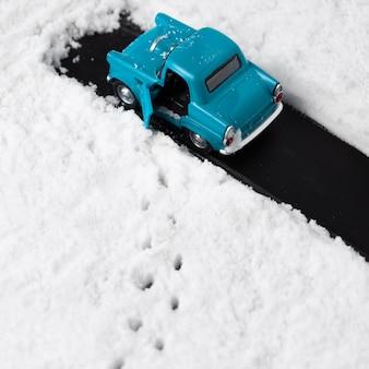 Vista cercana del coche de juguete azul con nieve