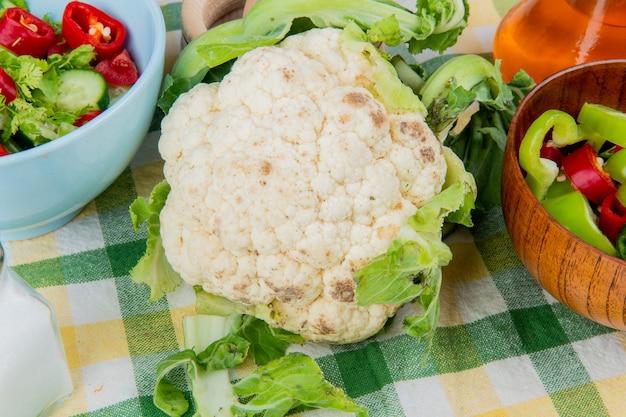 Vista cercana de coliflor con pimientos en rodajas y ensalada de verduras con mantequilla derretida y sal sobre tela escocesa