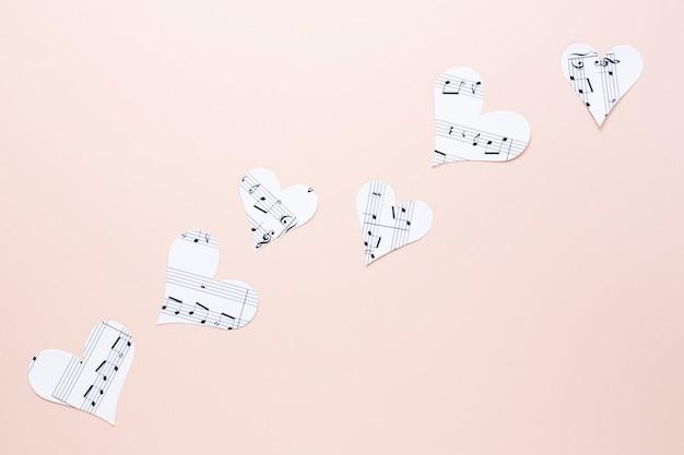 Vista cercana de corazones con notas musicales sobre fondo liso
