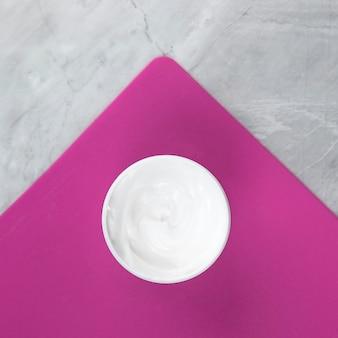 Vista cercana de una crema sobre fondo rosa y mármol