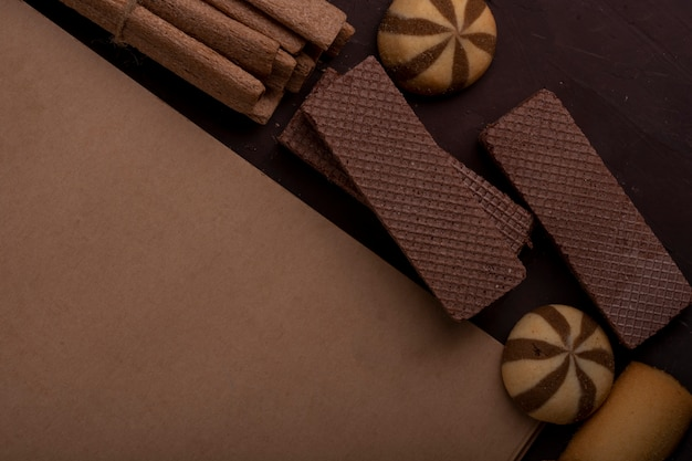Vista cercana del cuaderno de bocetos con diferentes galletas alrededor de maffins de pan de jengibre y palitos crujientes en la oscuridad