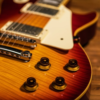 La vista cercana del cuerpo de la guitarra eléctrica está en el piso de madera