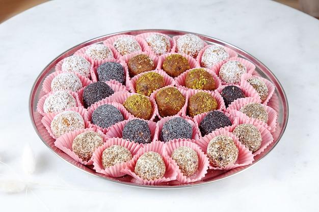 Vista cercana de diferentes conjuntos de dulces crudos, saludables, sin azúcar, veganos. tortas dulces para el menú de dieta. dulces sin gluten. bolas de caramelo crudo. tortas de bolas de energía en placa rosa. lay flat