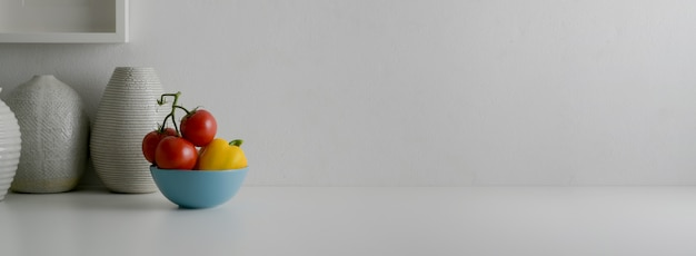 Vista cercana del diseñador de interiores moderno blanco con tazón de verduras, jarrones de cerámica y espacio de copia
