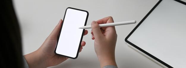 Vista cercana de la diseñadora femenina en busca de información sobre el teléfono inteligente maqueta horizontal