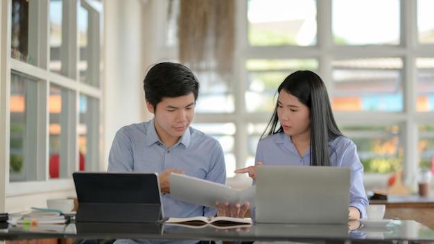 Vista cercana de dos empresarios informando sobre su proyecto en un espacio simple de trabajo conjunto
