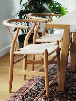 Vista cercana de dos sillas de madera cerca con mesa en un interior de comedor blanco con alfombra oriental. diseño de interiores en estilo minimalista.