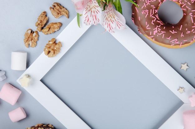 Vista cercana de dulces con nueces, galletas y flores en púrpura con espacio de copia