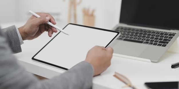 Vista cercana del empresario escribiendo su plan en tableta de pantalla en blanco en su oficina moderna
