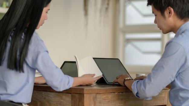 Vista cercana de empresarios que consultan sobre su proyecto con una computadora portátil en un espacio simple de trabajo conjunto