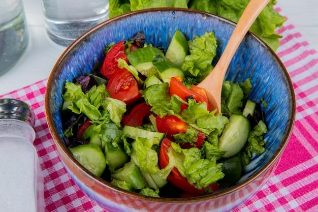Vista cercana de ensalada de verduras con sal sobre tela escocesa