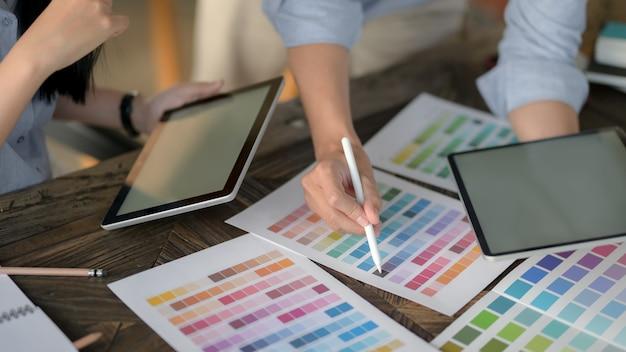 Vista cercana del equipo de diseñadores usando tableta digital mientras elige el color en la muestra de color en la mesa de madera vintage