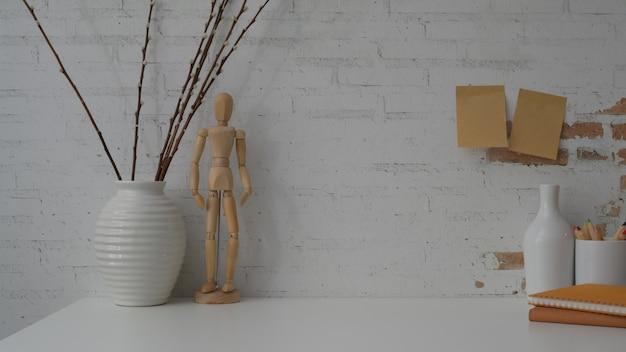 Vista cercana del espacio de trabajo contemporáneo en mesa blanca con pared de ladrillo blanco