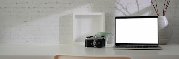Vista cercana del espacio de trabajo mínimo con pantalla en blanco portátil, cámara, decoraciones y copia espacio en la mesa blanca