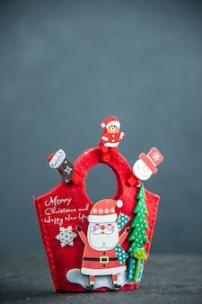 Vista cercana del estado de ánimo navideño con accesorios de decoración y caja de regalo de año nuevo en superficie oscura