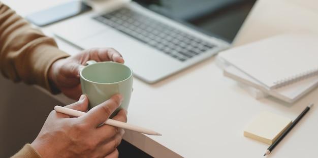 Vista cercana de freelance masculino sosteniendo una taza de café mientras trabajaba en una habitación cómoda