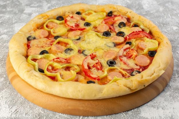 Vista cercana frontal de deliciosa pizza cursi con aceitunas, salchichas y tomates en la superficie gris