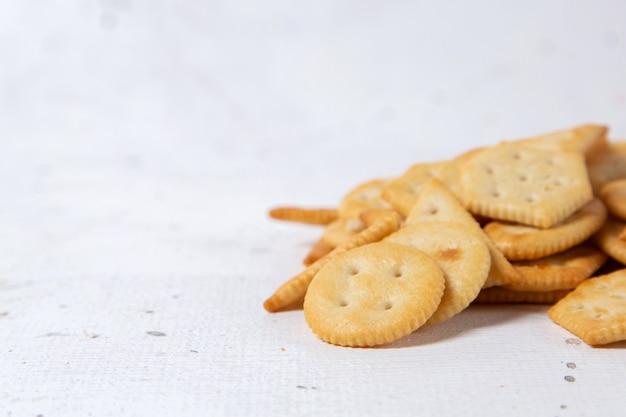 Vista cercana frontal formó galletas saladas aisladas en la superficie blanca