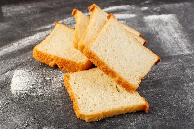 Vista cercana frontal panes blancos en rodajas y sabroso aislado en la superficie gris