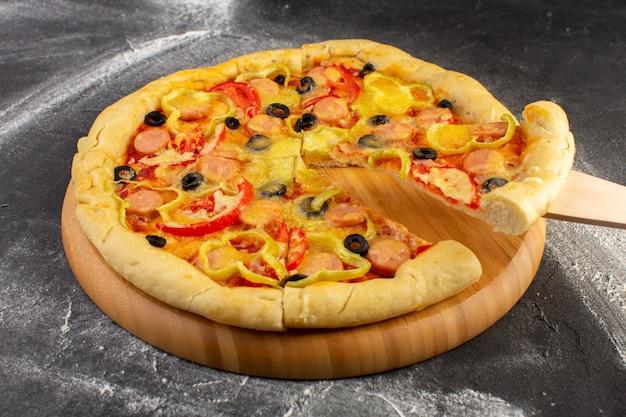 Vista cercana frontal sabrosa pizza cursi con tomates rojos, aceitunas negras, pimientos y salchichas en la superficie oscura