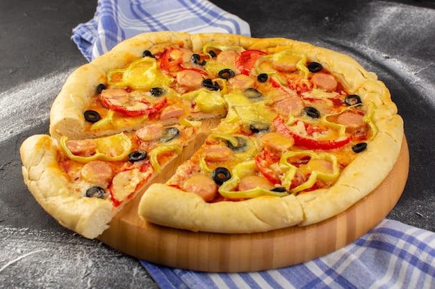 Vista cercana frontal sabrosa pizza cursi con tomates rojos, aceitunas negras y salchichas en el oscuro escritorio