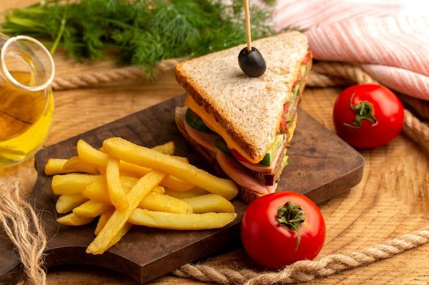 Vista cercana frontal sabroso sandwich con aceitunas, jamón y tomates junto con papas fritas